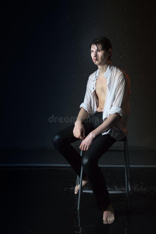 Retrato de la morenita atractiva del hombre joven en ropa mojada bajo gotitas de la lluvia Foto del estudio foto de archivo libre de regalías