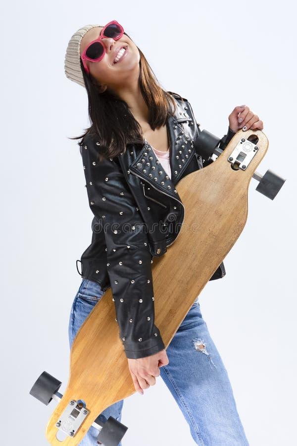 Retrato de la morenita caucásica sonriente feliz en chaqueta de cuero negra y las gafas de sol que presentan con Longboard imágenes de archivo libres de regalías
