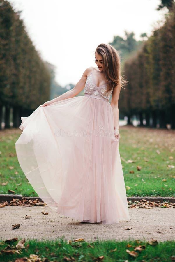Retrato de la morenita hermosa en vestido largo de la rosa de la gasa fotos de archivo libres de regalías