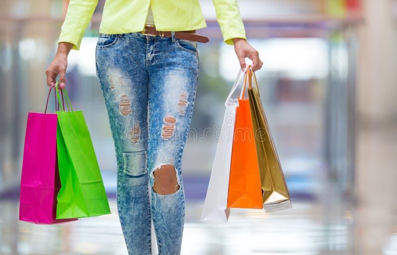 Retrato de la morenita sonriente atractiva en alameda de compras con una tarjeta de crédito de los bolsos en una mano fotos de archivo