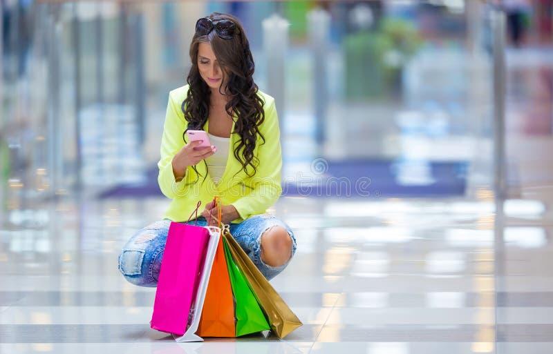 Retrato de la morenita sonriente atractiva en alameda de compras con una tarjeta de crédito de los bolsos en una mano foto de archivo