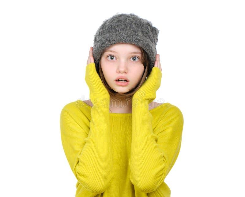 Retrato de la muchacha adolescente asustada sorprendida en un sombrero hecho punto fotografía de archivo