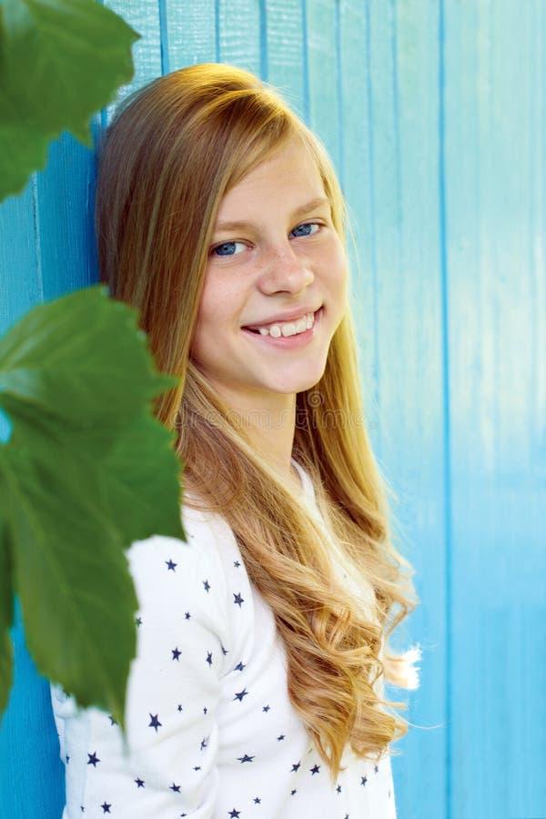 Retrato de la muchacha adolescente bonita en fondo de madera azul de la pared fotografía de archivo