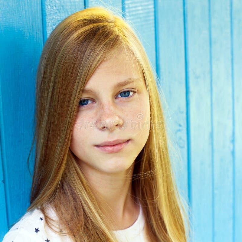 Retrato de la muchacha adolescente bonita en fondo de madera azul de la pared foto de archivo