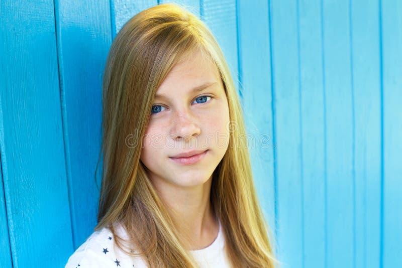 Retrato de la muchacha adolescente bonita en fondo de madera azul de la pared fotografía de archivo libre de regalías