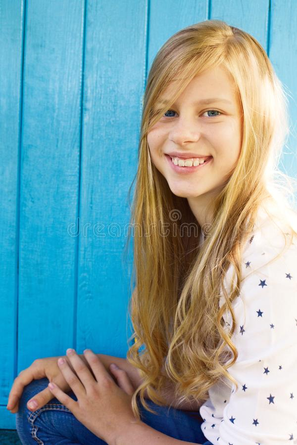 Retrato de la muchacha adolescente bonita en fondo de madera azul de la pared foto de archivo libre de regalías