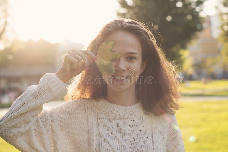 Retrato de la muchacha adolescente con la hoja de arce foto de archivo