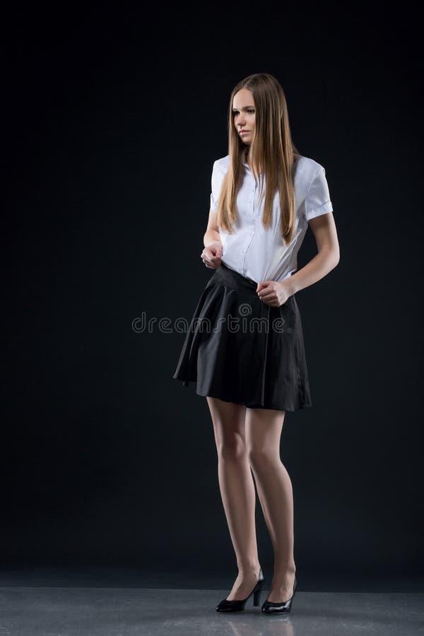 Retrato de la muchacha adolescente en el fondo negro que presenta en una blusa blanca y una falda negra corta, mirada de la ofici imagen de archivo