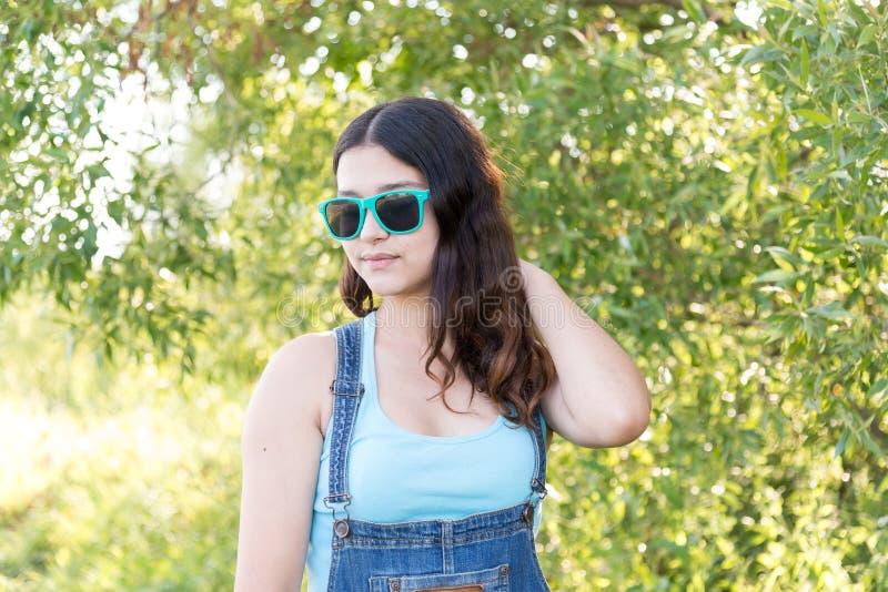 Retrato de la muchacha adolescente en gafas de sol el verano de la naturaleza imagen de archivo libre de regalías