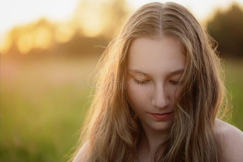 Retrato de la muchacha adolescente en la puesta del sol que mira abajo imagen de archivo libre de regalías