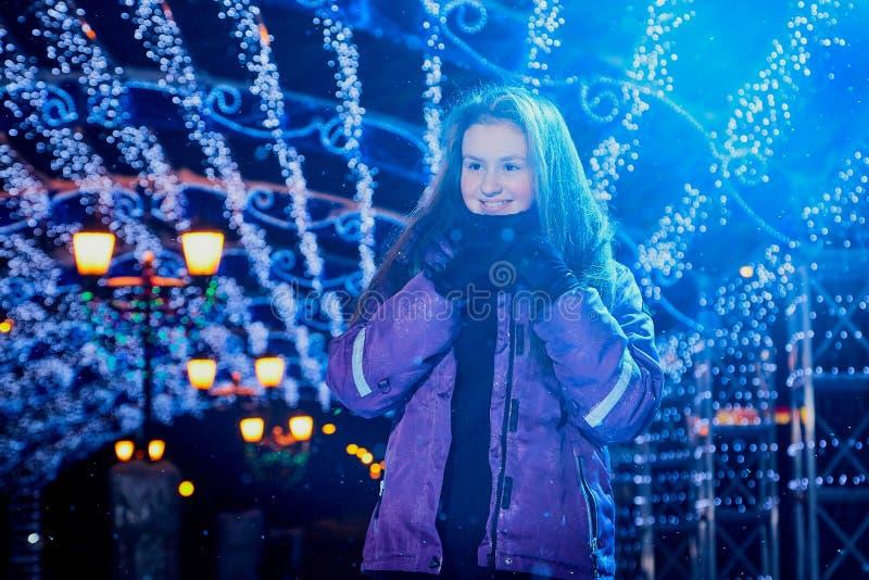 Retrato de la muchacha adolescente en la pista de patinaje de la ciudad con las luces brillantes en el fondo por la tarde fotografía de archivo