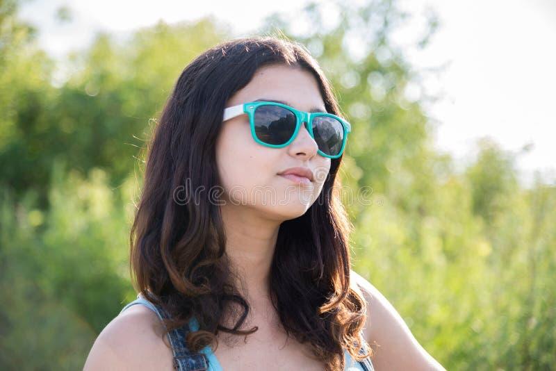 Retrato de la muchacha adolescente hermosa en gafas de sol foto de archivo