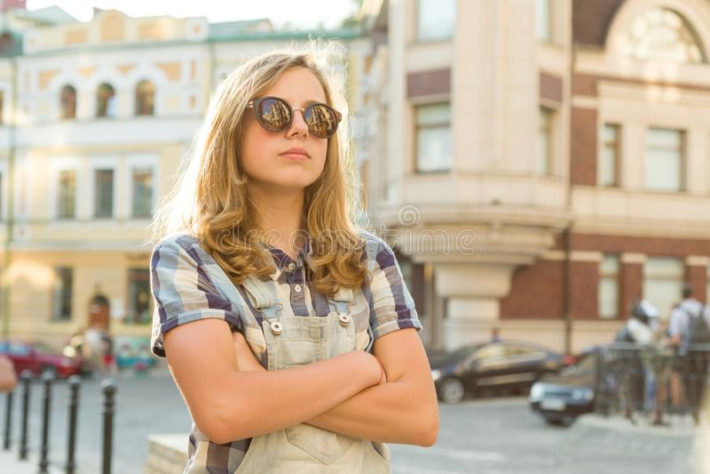 Retrato de la muchacha adolescente infeliz triste con las manos dobladas en la calle de la ciudad, espacio de la copia fotografía de archivo