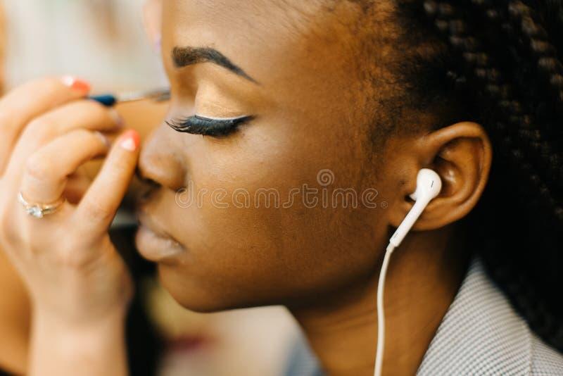 Retrato de la muchacha africana hermosa joven que escucha la música y que recibe el maquillaje de maquillaje profesional imagenes de archivo