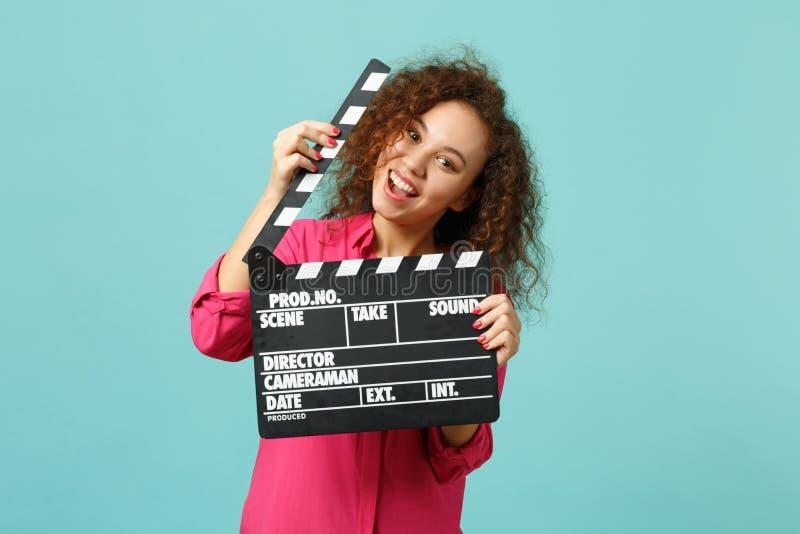 Retrato de la muchacha africana loca en la ropa casual que sostiene clapperboard negro clásico del rodaje de películas aislado en fotos de archivo