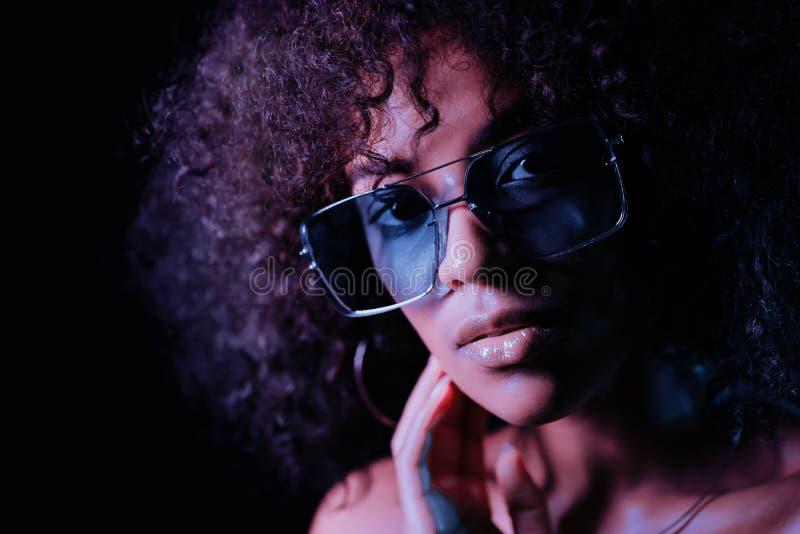 Retrato de la muchacha afroamericana atractiva joven en la luz de ne?n en el fondo negro Mujer de tentaci?n con maquillaje perfec imagen de archivo