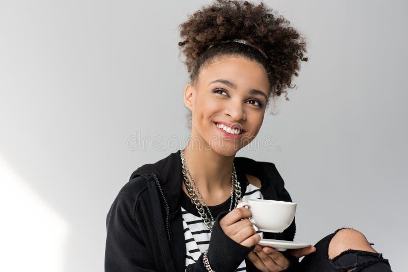 Retrato de la muchacha afroamericana joven que sostiene la taza de té aislada fotos de archivo