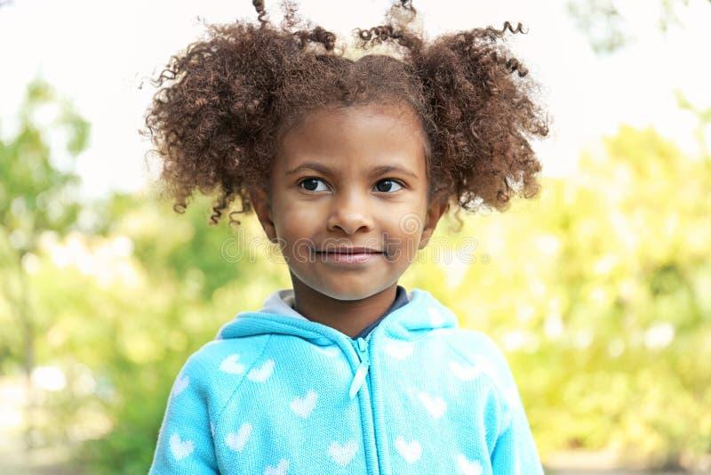 Retrato de la muchacha afroamericana linda en fondo natural borroso fotografía de archivo libre de regalías