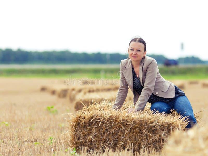 Retrato de la muchacha agradable con una paja en un campo foto de archivo libre de regalías