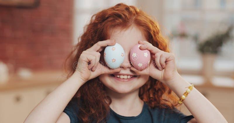 Retrato de la muchacha alegre del niño del pelirrojo que juega con el huevo de Pascua en el fondo de la cocina Ella está animando foto de archivo
