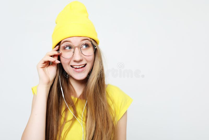 Retrato de la muchacha alegre hermosa con los auriculares con la risa sonriente del pelo largo mirando la cámara foto de archivo