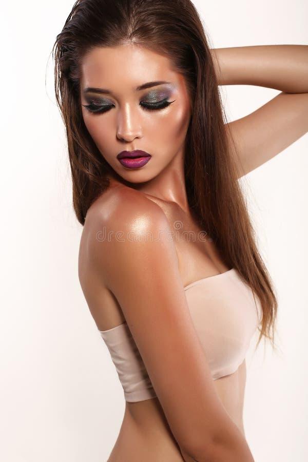 Retrato de la muchacha asiática atractiva de la mirada con el pelo oscuro y el maquillaje brillante fotos de archivo libres de regalías