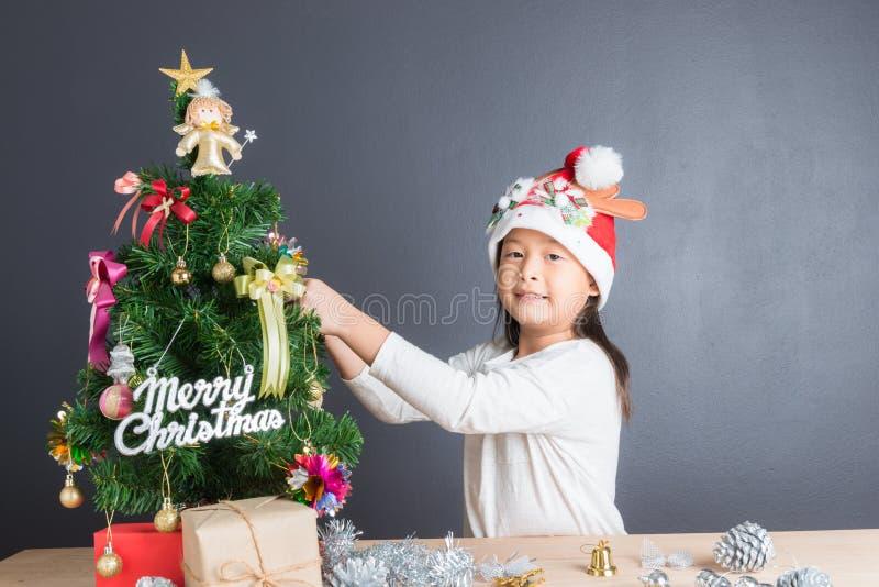 Retrato de la muchacha asiática feliz que adorna poco árbol de navidad imagen de archivo libre de regalías