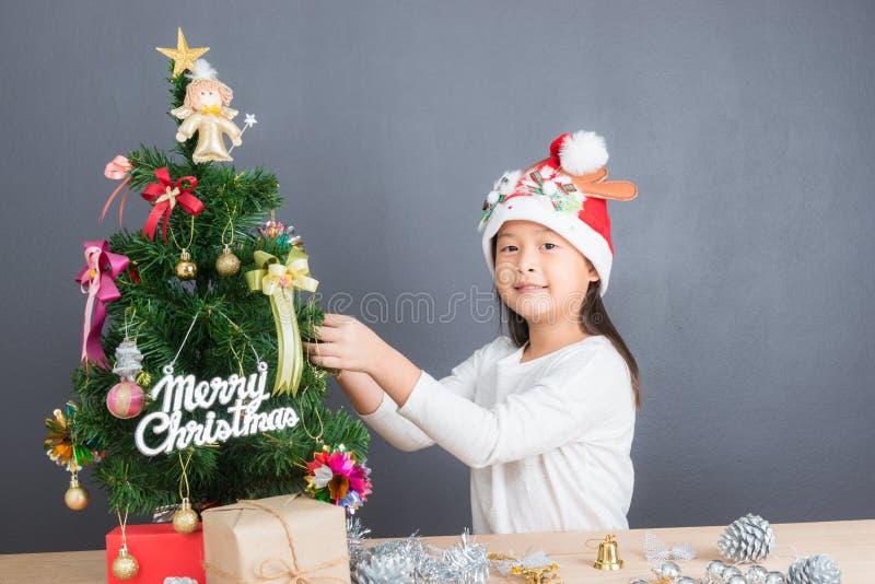 Retrato de la muchacha asiática feliz que adorna poco árbol de navidad fotografía de archivo