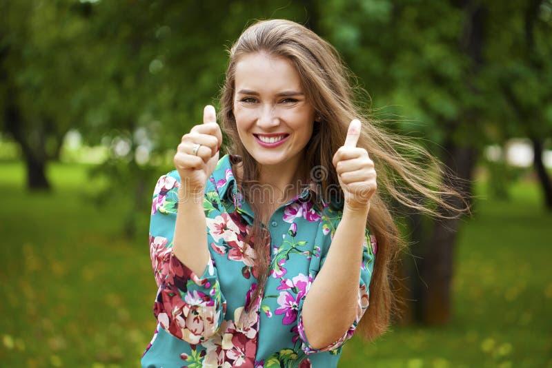Retrato de la muchacha asiática hermosa joven que muestra los pulgares para arriba imagen de archivo libre de regalías