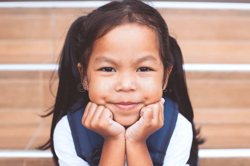 Retrato de la muchacha asiática linda del niño con la sonrisa del bolso de escuela imagen de archivo