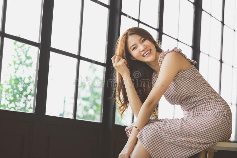 Retrato de la muchacha asiática linda y hermosa que sonríe en cafetería u oficina moderna con el espacio de la copia Gente feliz, imagen de archivo