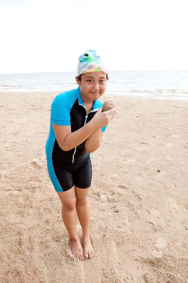 Retrato de la muchacha asiática que juega en la playa de la arena con la emoción feliz de la cara foto de archivo libre de regalías