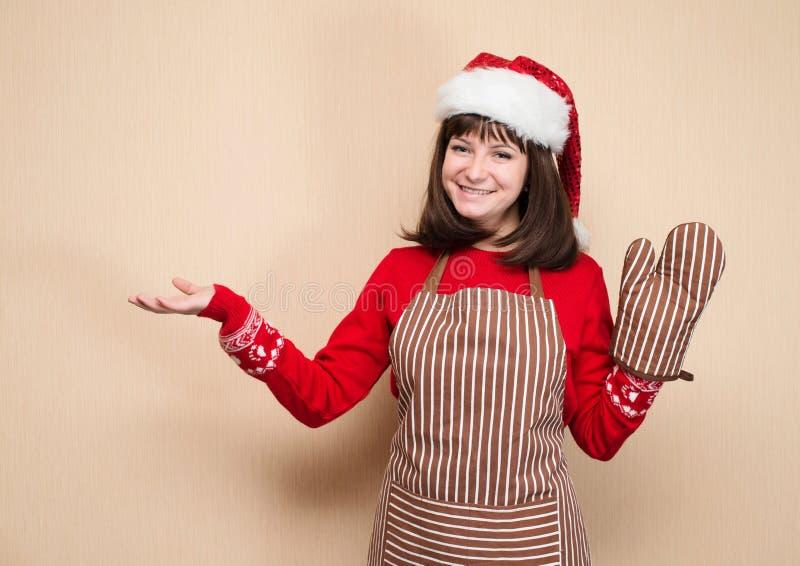 Retrato de la muchacha atractiva en delantal del cocinero, guante del horno y Cristo fotos de archivo libres de regalías