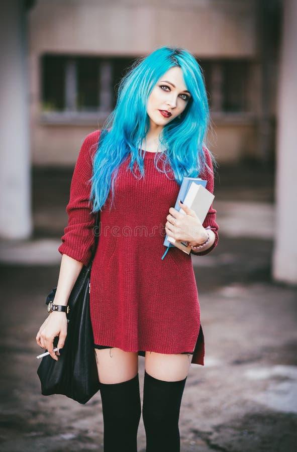 Retrato de la muchacha azul-cabelluda sonriente linda de la roca del grunge con los libros y el cigarrillo en manos imágenes de archivo libres de regalías