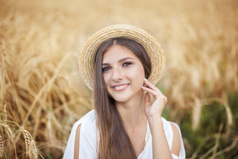 Retrato de la muchacha de la belleza en campo de trigo en la puesta del sol Mujer joven atractiva que sonríe y que disfruta de vi imagen de archivo