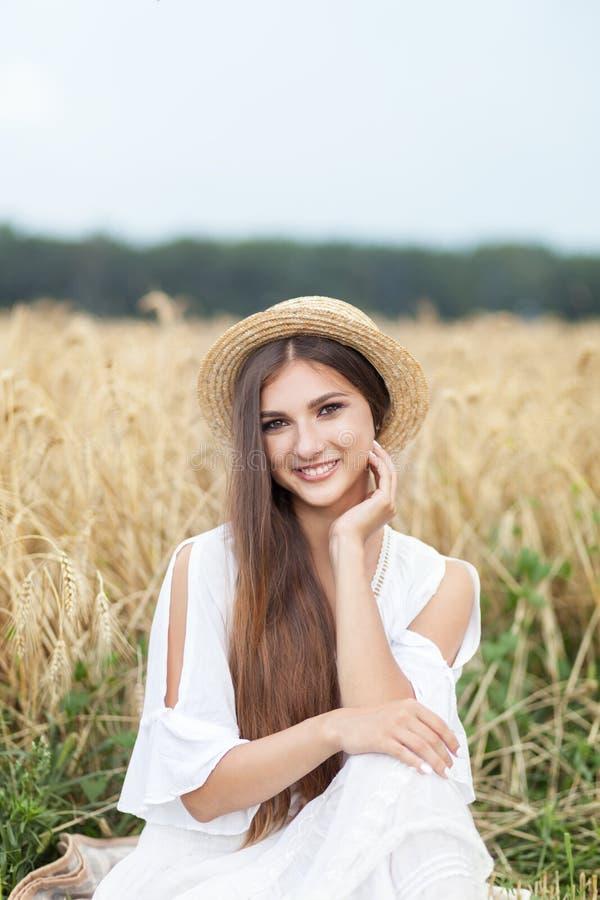 Retrato de la muchacha de la belleza en campo de trigo en la puesta del sol Mujer joven atractiva que sonríe y que disfruta de vi fotografía de archivo libre de regalías