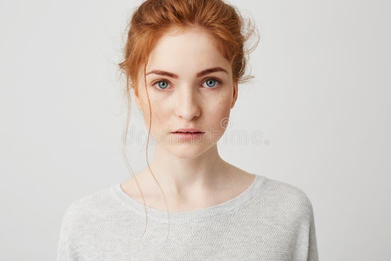 Retrato de la muchacha blanda hermosa del jengibre con los ojos azules que presentan mirando la cámara sobre el fondo blanco foto de archivo