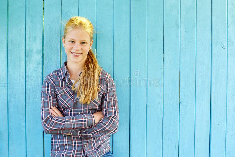 Retrato de la muchacha bonita en fondo de madera azul de la pared foto de archivo