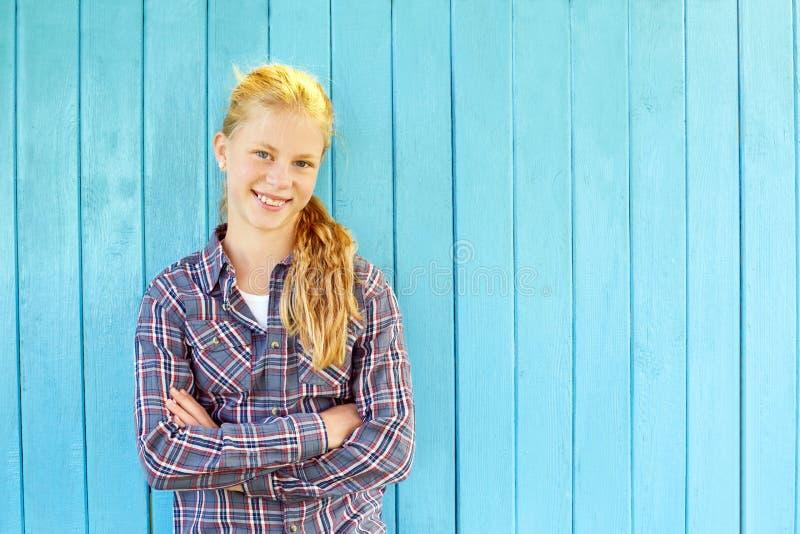 Retrato de la muchacha bonita en fondo de madera azul de la pared fotografía de archivo