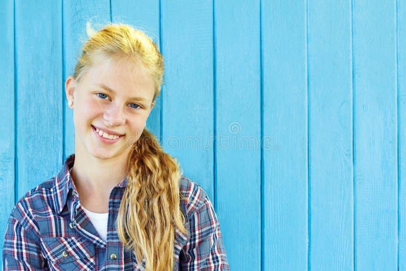 Retrato de la muchacha bonita en fondo de madera azul de la pared fotos de archivo
