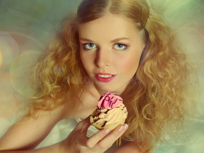 Retrato de la muchacha bonita que come la torta imagen de archivo
