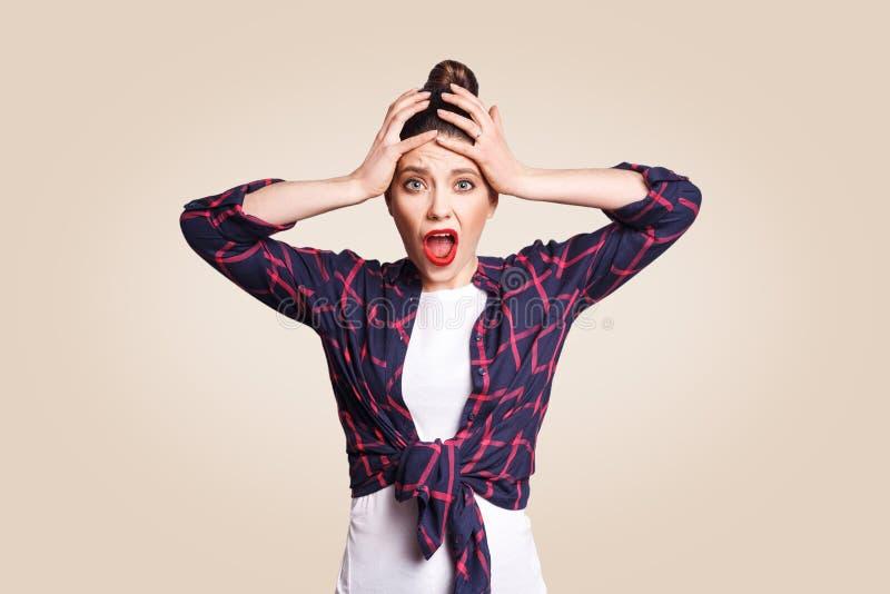 Retrato de la muchacha caucásica histérica con el pelo del bollo que mira en la desesperación y el pánico, siendo atrasado para e foto de archivo