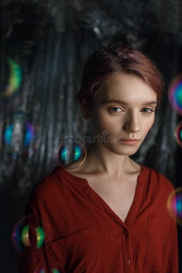 Retrato de la muchacha caucásica joven bonita en camisa roja Las burbujas de jabón vuelan alrededor de su cabeza que riela con co foto de archivo
