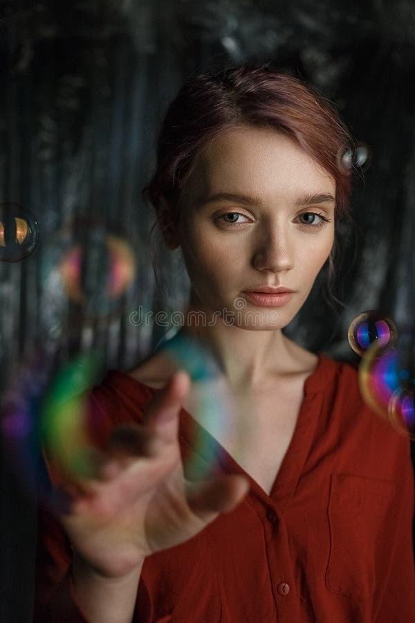 Retrato de la muchacha caucásica joven flaca en camisa roja Las burbujas de jabón vuelan alrededor de su cabeza que riela con col fotografía de archivo libre de regalías