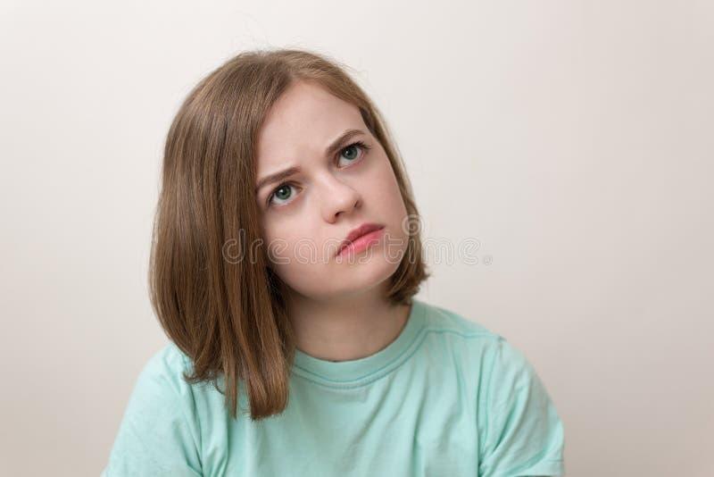 Retrato de la muchacha caucásica joven de la mujer con la expresión que pregunta, desconcertada, confusa, pensando o recordando a imagenes de archivo