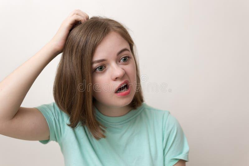 Retrato de la muchacha caucásica joven de la mujer con preguntar, expresión desconcertada, confusa, perpleja imagenes de archivo