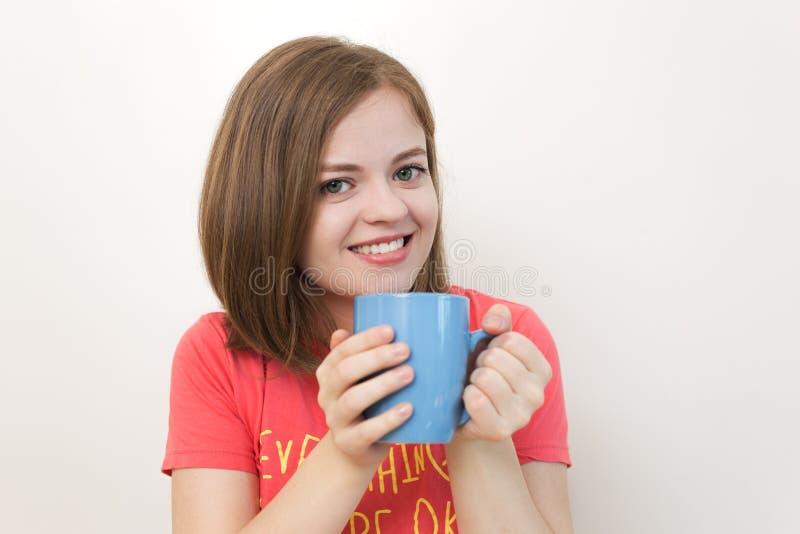 Retrato de la muchacha caucásica joven sonriente de la mujer que sostiene una taza de café con ambas manos como si diga: ¡Buenos  foto de archivo