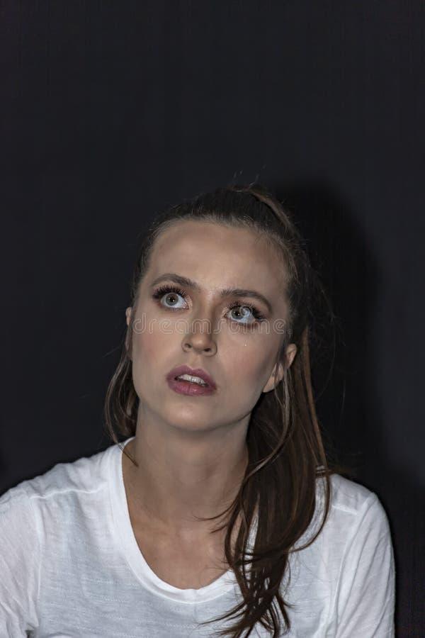 Retrato de la muchacha con un pelo largo y ojos verdes en la camiseta blanca que mira hacia arriba Fondo negro fotos de archivo libres de regalías