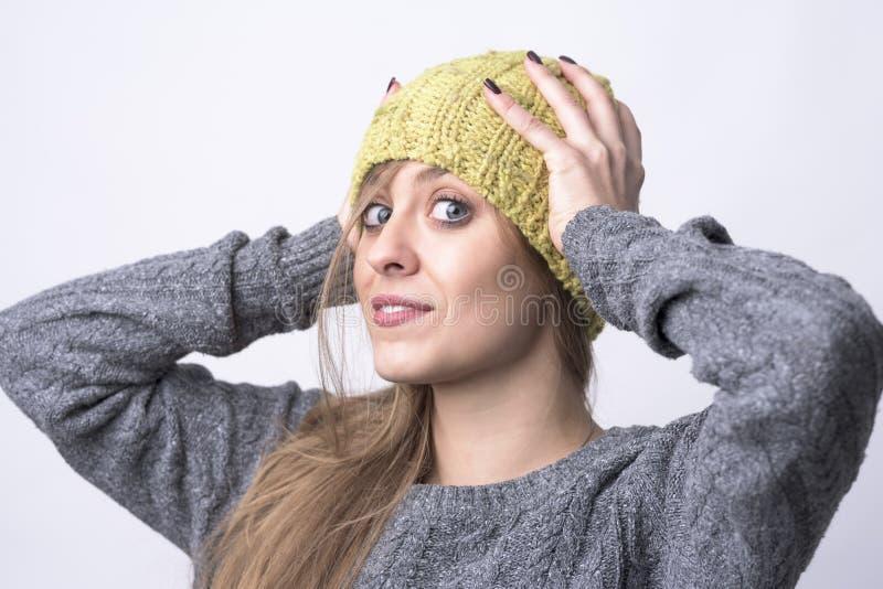 Retrato de la muchacha confiada joven linda que intenta en el casquillo hecho punto amarillo para el tiempo frío del invierno fotos de archivo libres de regalías