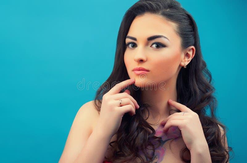 Retrato de la muchacha contemplativa hermosa en el fondo azul imagen de archivo